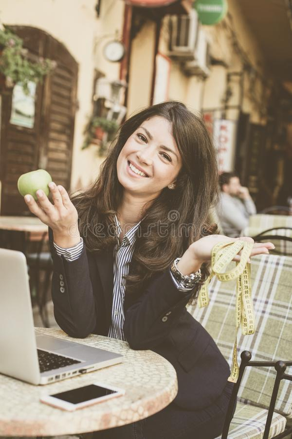 Glimlachende vrouw met appel en meter in handen royalty-vrije stock foto's