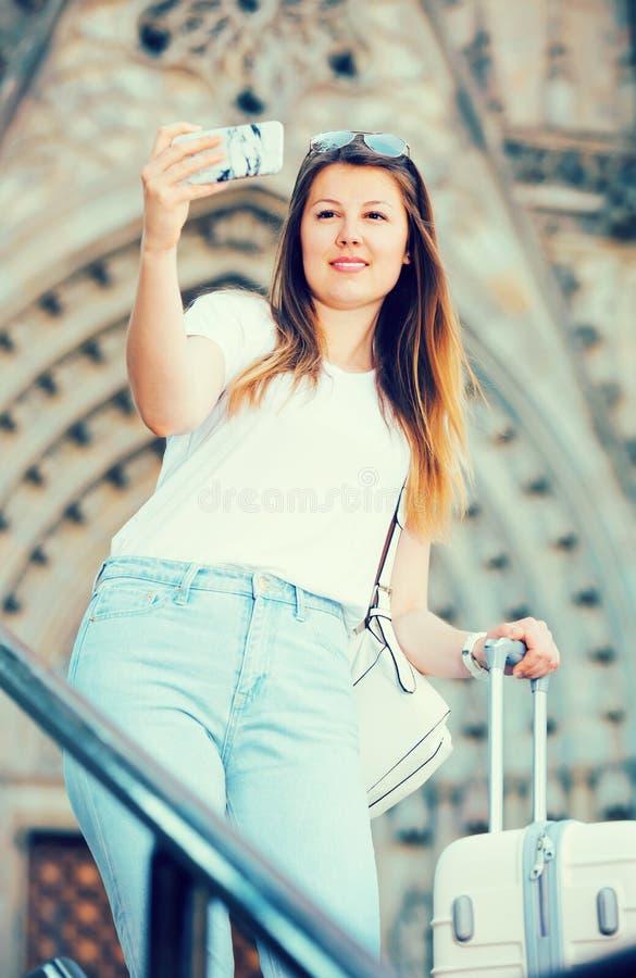 Glimlachende vrouw met bagage die selfie doen royalty-vrije stock fotografie
