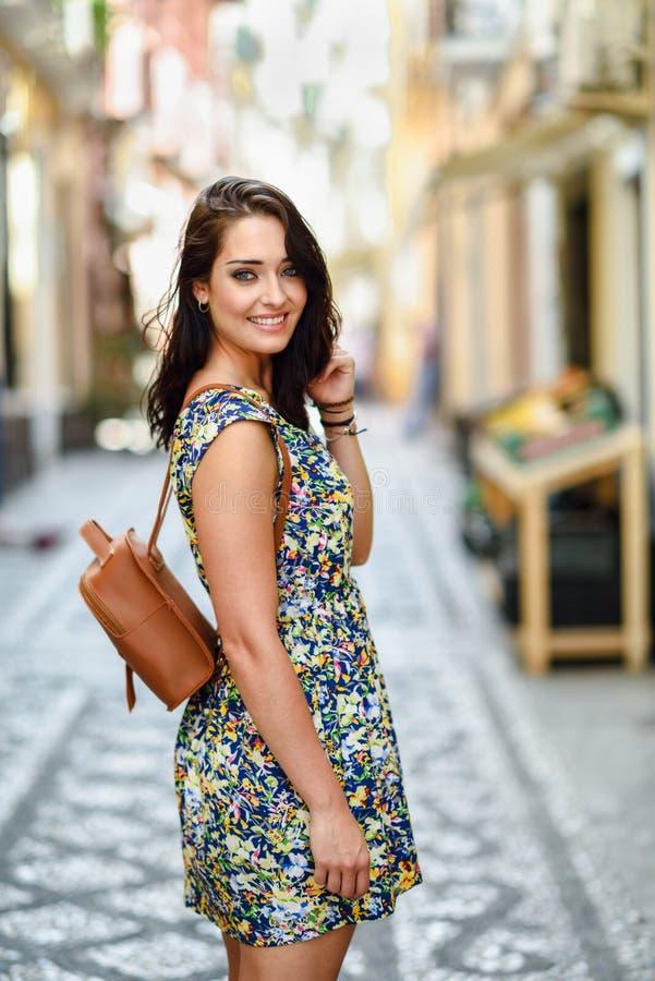 Glimlachende vrouw met blauwe ogen met bruin golvend haar in openlucht Meisje die bloemkleding op stedelijke achtergrond dragen S stock fotografie