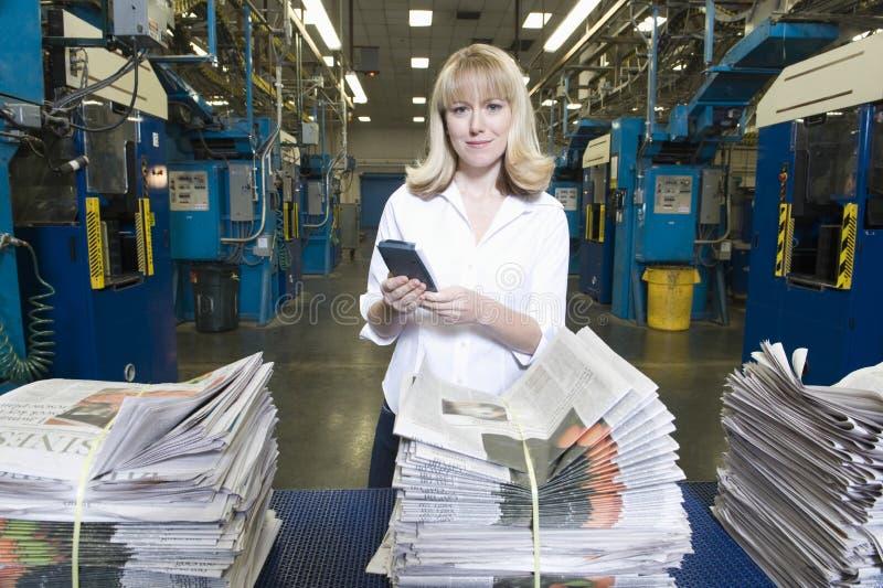 Glimlachende Vrouw met Calculator in Fabriek stock afbeeldingen