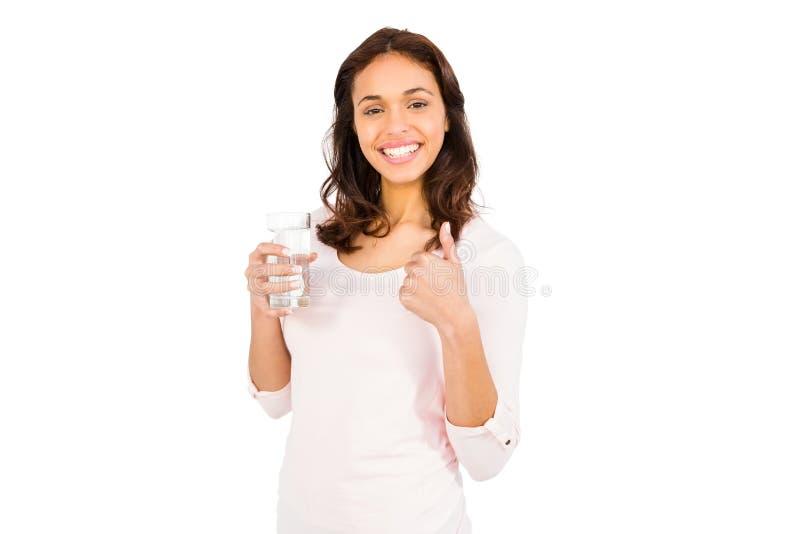 Glimlachende vrouw met duimen op holdingsglas water stock afbeelding