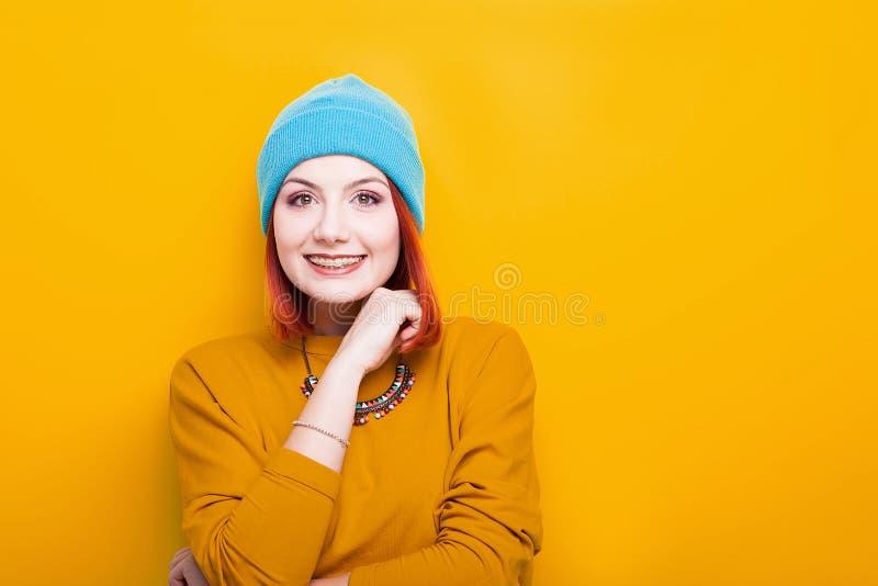 Glimlachende vrouw met een blauwe hoed die en camera glimlachen bekijken stock afbeeldingen