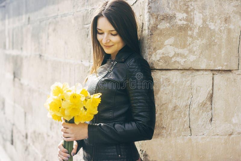 Glimlachende vrouw met een bos van bloemen Zonnige dag royalty-vrije stock foto