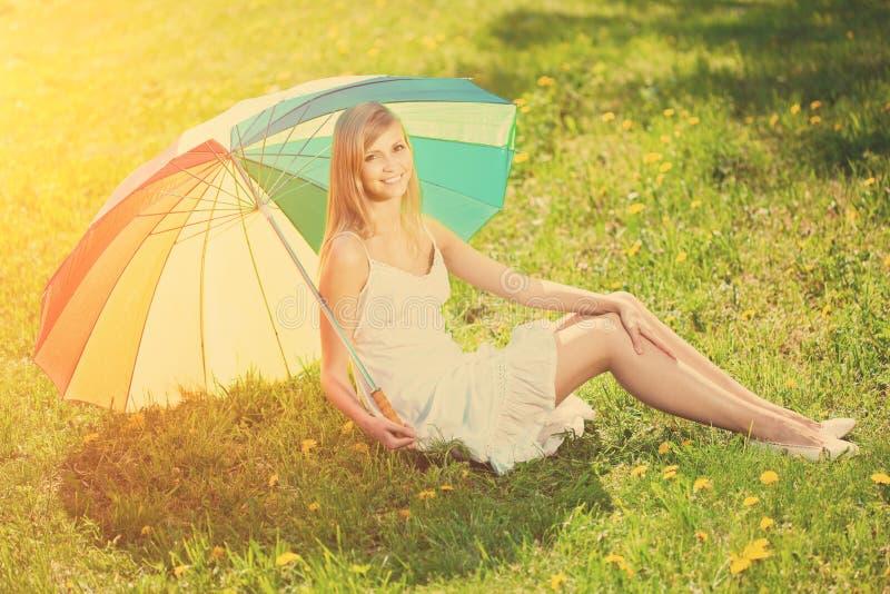 Glimlachende vrouw met een regenboogparaplu in openlucht stock fotografie