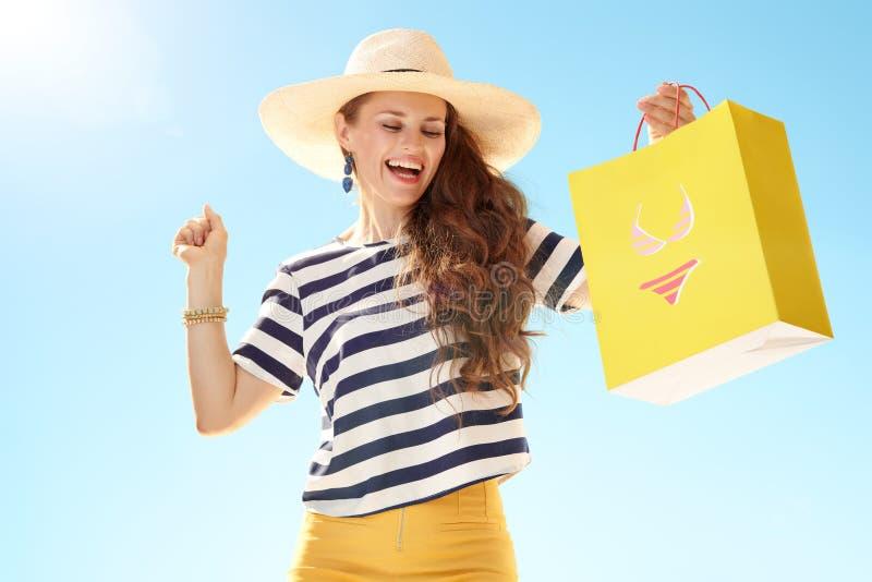 Glimlachende vrouw met gele het winkelen zak met bikini het dansen stock foto