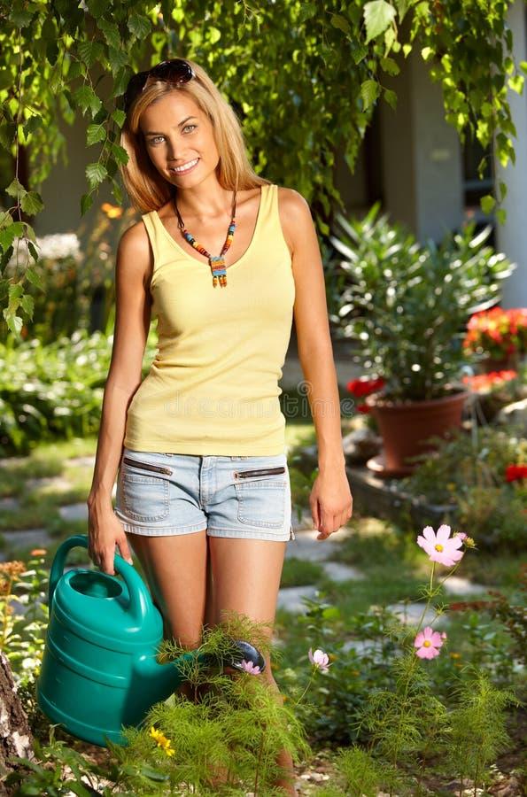 Glimlachende vrouw met gieter in de tuin stock fotografie