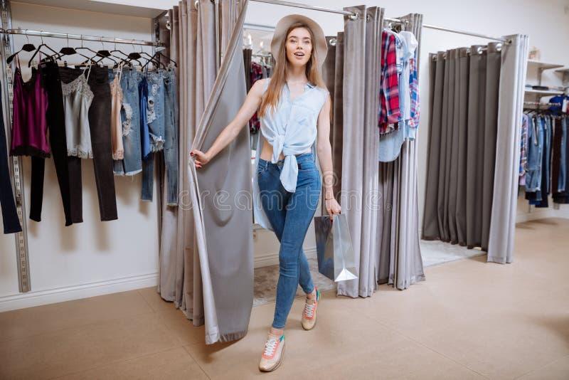 Glimlachende vrouw met het winkelen zak het uitgaan van montageruimte royalty-vrije stock fotografie