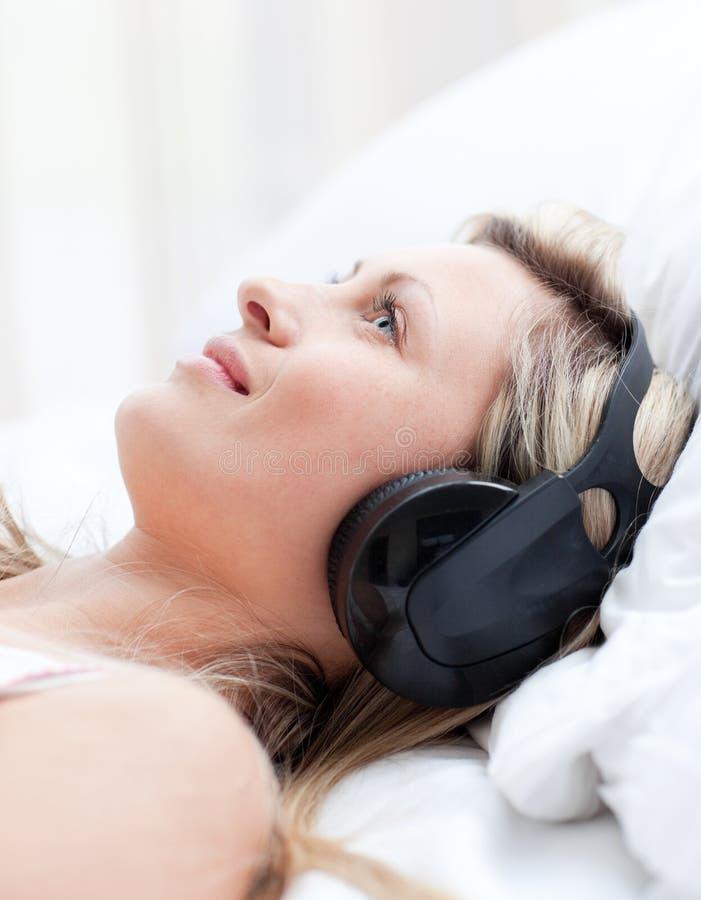 Glimlachende vrouw met hoofdtelefoons bij het liggen op een bed stock afbeelding