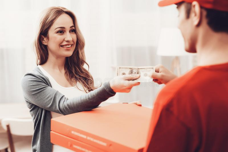 Glimlachende Vrouw met Koerier Pizza Delivery Payment stock afbeelding