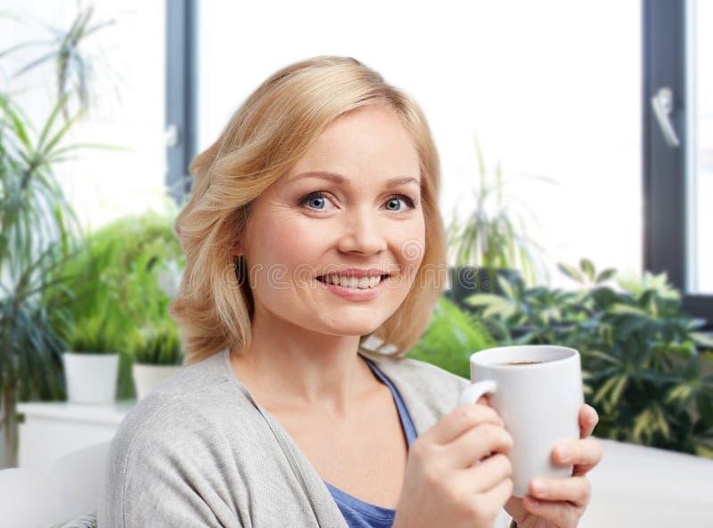 Glimlachende vrouw met kop thee of koffie thuis royalty-vrije stock afbeelding