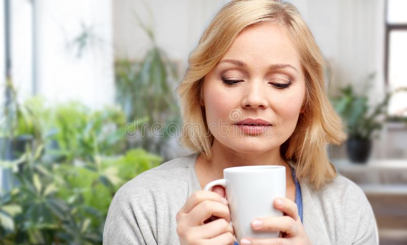 Glimlachende vrouw met kop thee of koffie thuis stock foto's