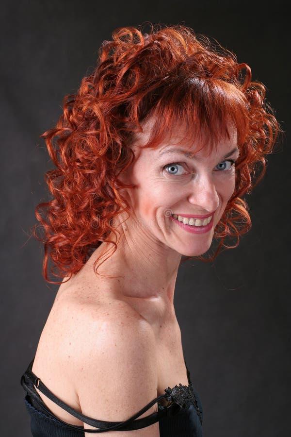 Glimlachende vrouw met krullend haar royalty-vrije stock afbeeldingen
