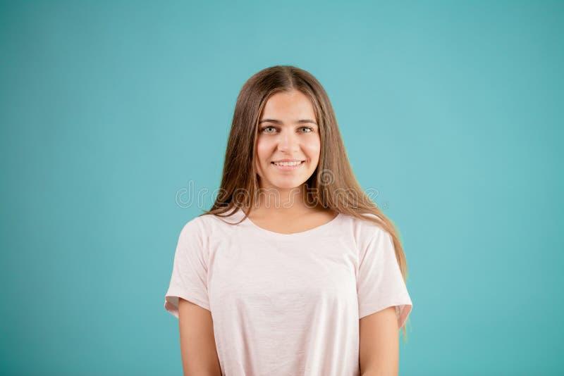 Glimlachende vrouw met lang streight bruin haar in wit T -t-shit stock fotografie