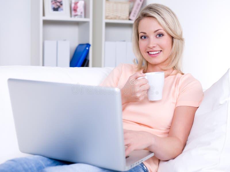 Glimlachende vrouw met laptop en kop van koffie stock afbeelding