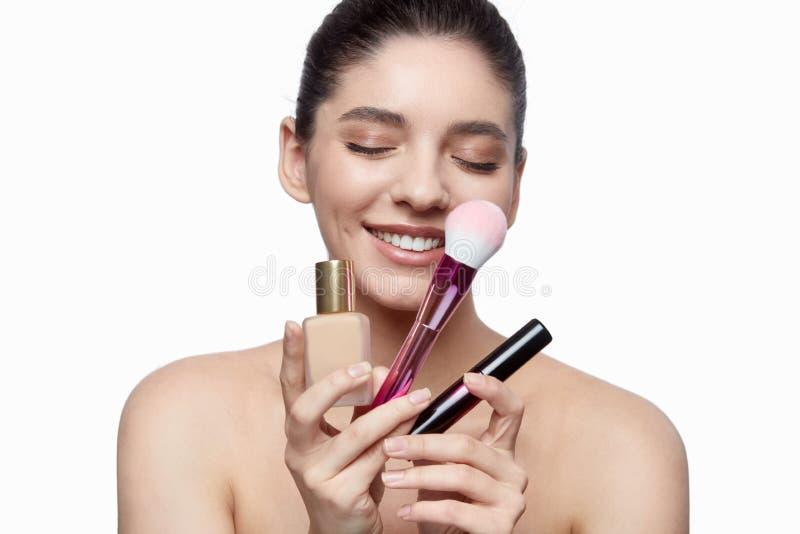 Glimlachende vrouw met make-uphulpmiddelen stock afbeeldingen