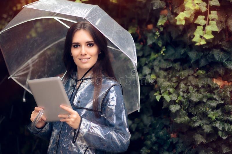 Glimlachende Vrouw met Regenjas en Paraplu de Tablet van Holdingspc royalty-vrije stock afbeelding