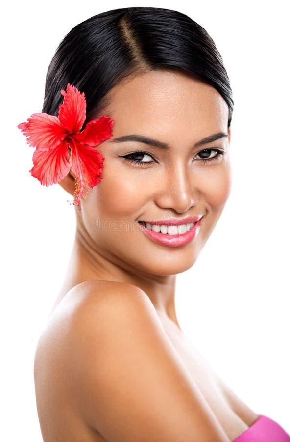 Glimlachende vrouw met rode bloem royalty-vrije stock afbeelding