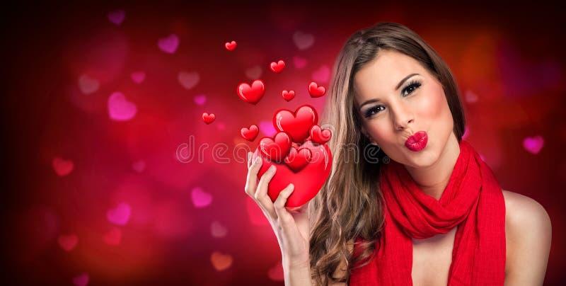 Glimlachende vrouw met rood hart stock fotografie