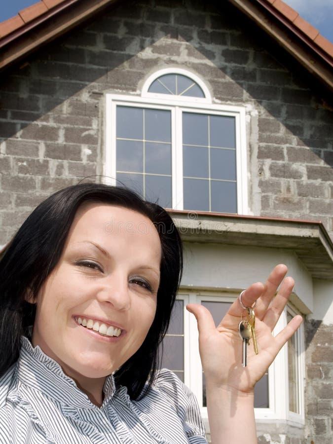 Glimlachende vrouw met sleutels tot het huis stock foto's