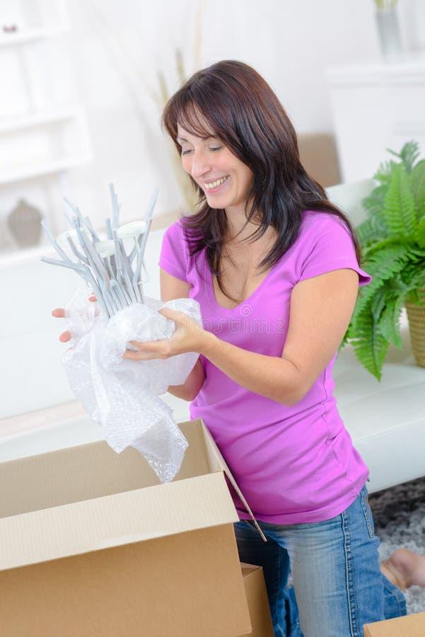 Glimlachende vrouw met vele kartondozen die zich aan nieuwe plaats bewegen stock foto's