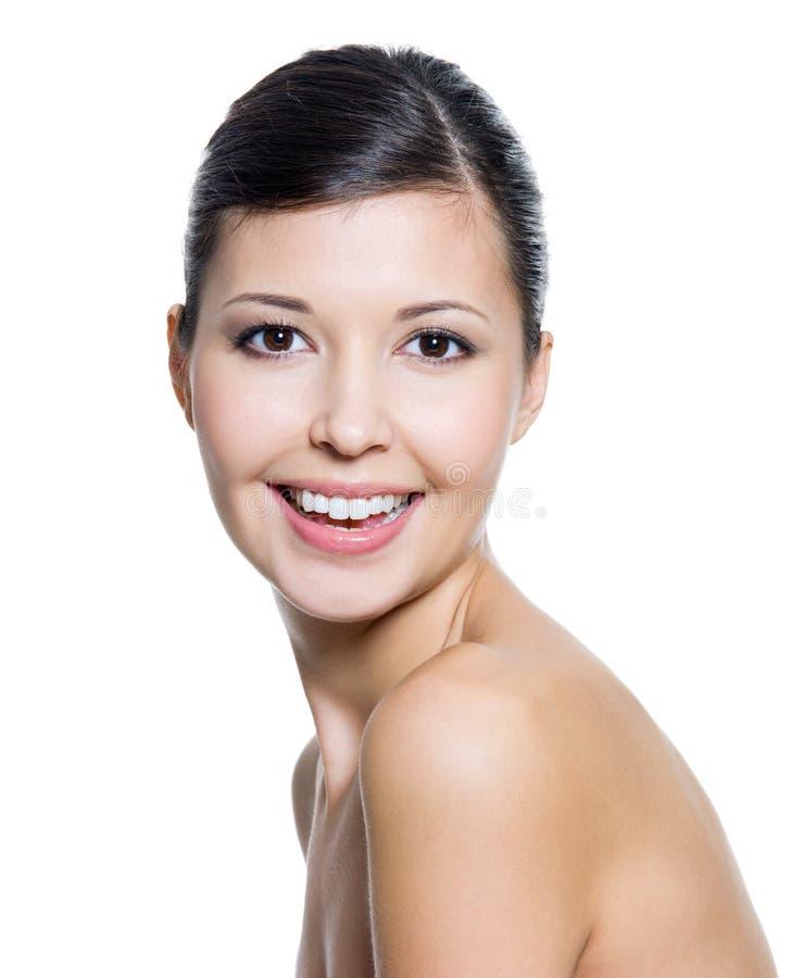 Glimlachende vrouw met verse gezonde huid van een gezicht stock foto