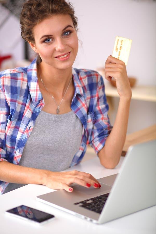 Glimlachende vrouw online het winkelen gebruikende computer en creditcard in keuken royalty-vrije stock fotografie