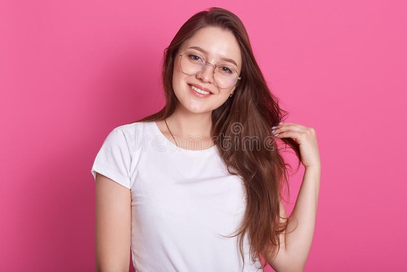 Glimlachende vrouw in oogglazen die in studio tegen roze muur stellen die direct camera, schuine standenhoofd en aanrakingen beki stock foto