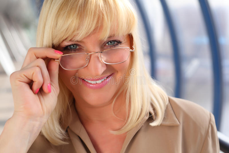 Glimlachende vrouw op middelbare leeftijd in glazen royalty-vrije stock afbeeldingen