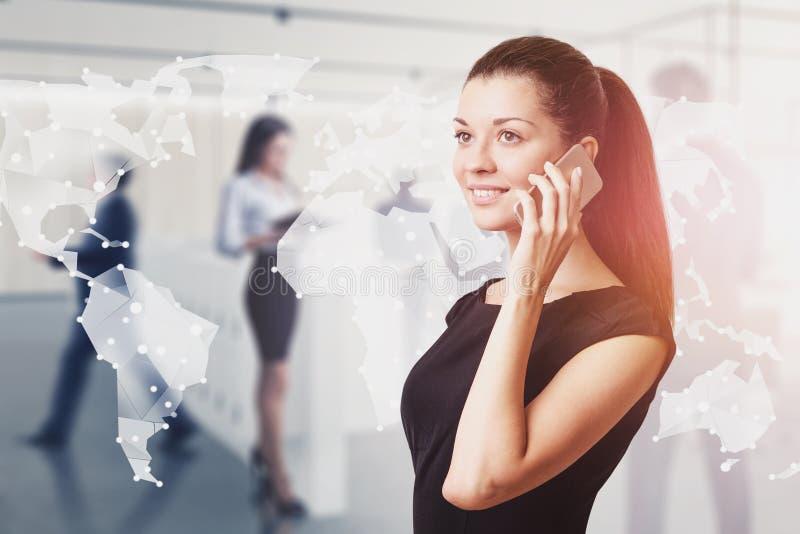 Glimlachende vrouw op telefoon in bureau, wereldnetwerk stock fotografie