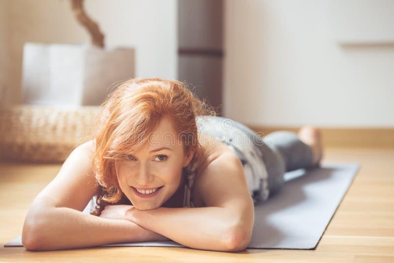 Glimlachende vrouw op yogamat royalty-vrije stock fotografie