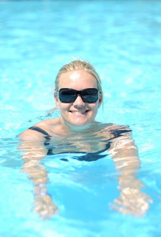 Glimlachende vrouw in pool stock foto