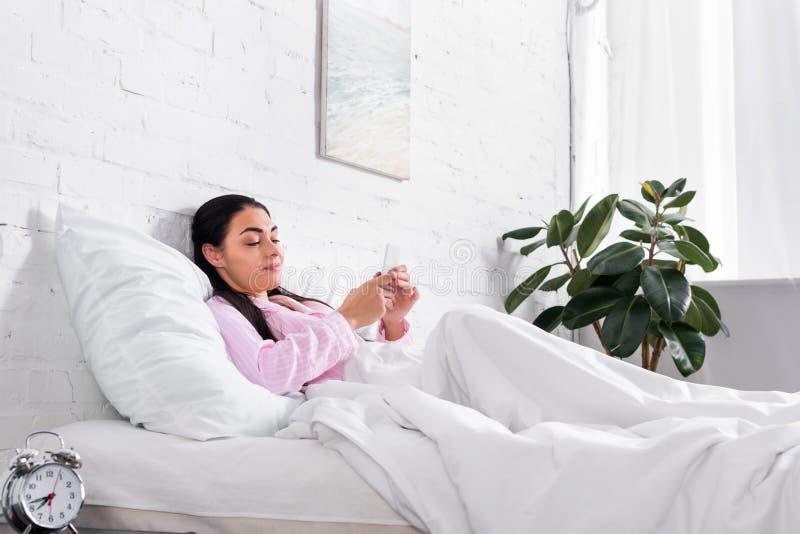 glimlachende vrouw in pyjama's die smartphone gebruiken terwijl het rusten in bed stock afbeelding