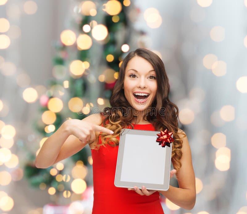Glimlachende vrouw in rode kleding met tabletpc stock foto