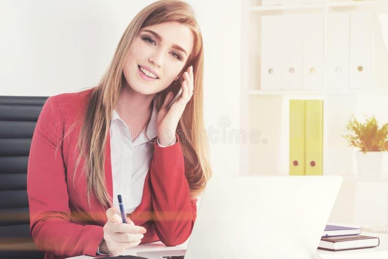 Glimlachende vrouw in rood op telefoon in bureau royalty-vrije stock afbeelding