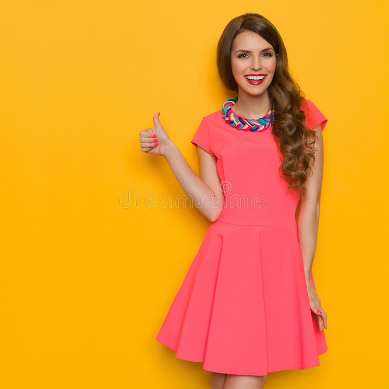 Glimlachende Vrouw in Roze Mini Dress Gives Like stock afbeeldingen