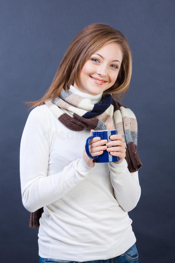 Glimlachende vrouw in sjaal met kop thee stock foto's