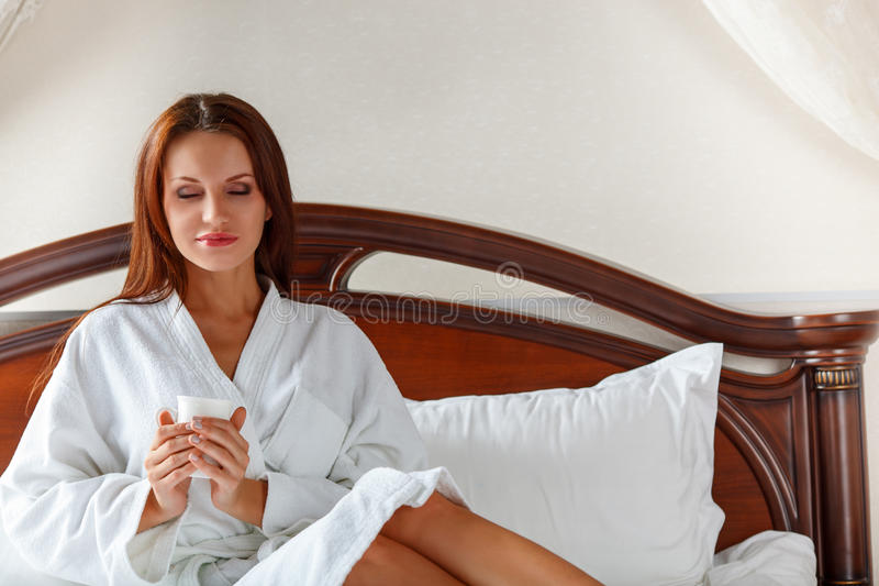 Glimlachende vrouw in slaapkamer het drinken koffie op bed stock afbeeldingen