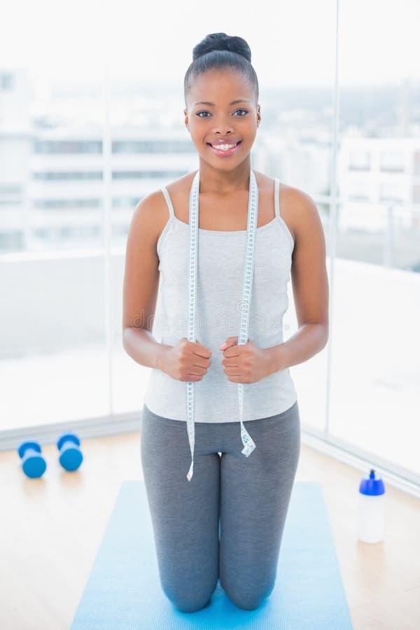 Glimlachende vrouw in sportkledingsholding die band meten rond haar hals royalty-vrije stock foto's