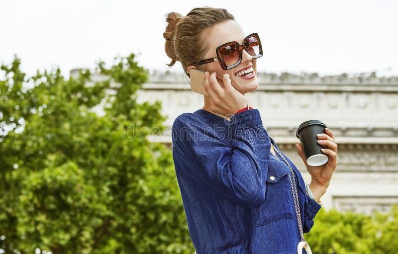 Glimlachende vrouw terwijl het drinken van koffie op Champ Elysses in Parijs stock afbeelding