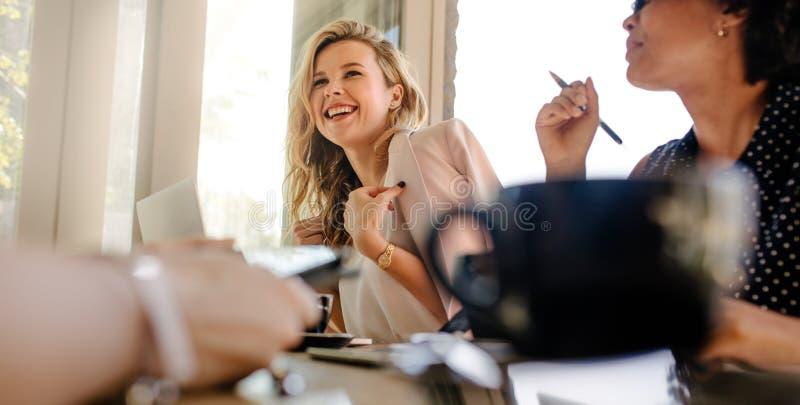 Glimlachende vrouw in vergadering met collega's stock fotografie