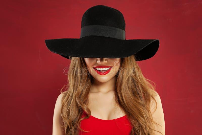 Glimlachende vrouw in zwarte hoed op rode achtergrond Mooi gelukkig modelportret royalty-vrije stock fotografie