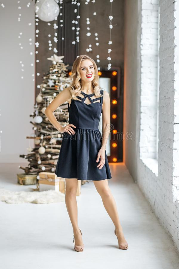 Glimlachende vrouw in zwarte kleding en gehielde schoenen Concept gelukkig royalty-vrije stock fotografie