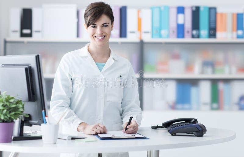 Glimlachende vrouwelijke arts die bij de kliniek werken royalty-vrije stock afbeelding