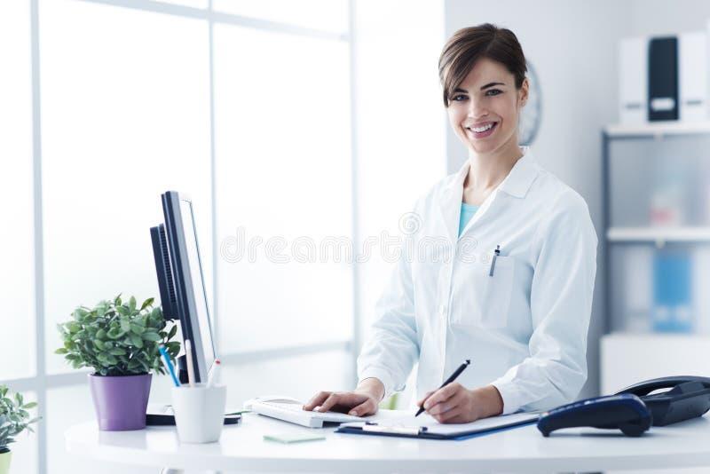 Glimlachende vrouwelijke arts die bij de kliniek werken stock afbeelding