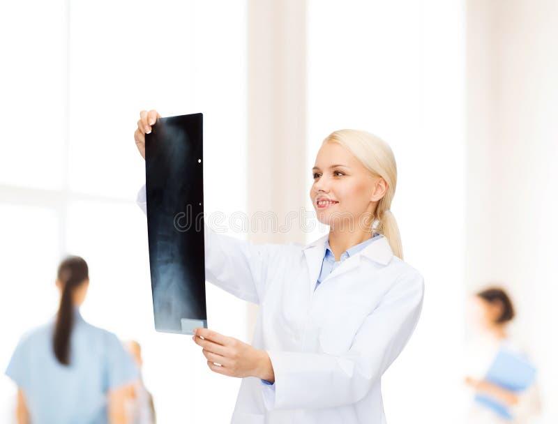 Glimlachende vrouwelijke arts die Röntgenstraal bekijkt royalty-vrije stock afbeeldingen