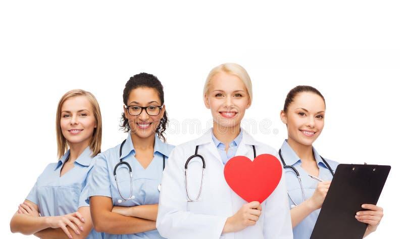Glimlachende vrouwelijke arts en verpleegsters met rood hart stock foto's