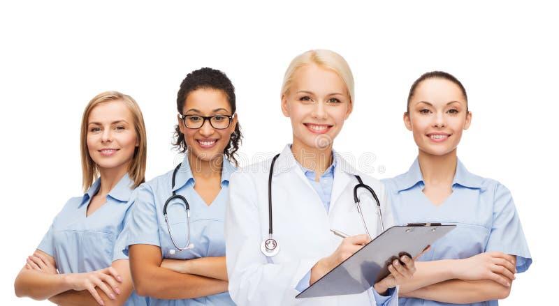 Glimlachende vrouwelijke arts en verpleegsters met stethoscoop royalty-vrije stock foto's