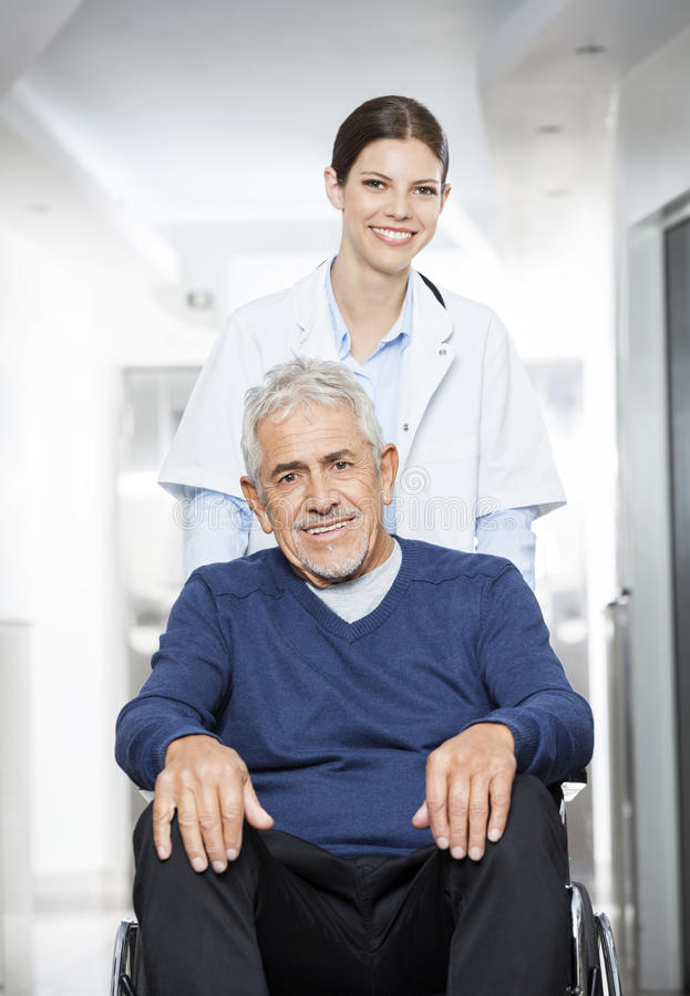 Glimlachende Vrouwelijke Arts Pushing Senior Patient als Wielvoorzitter stock fotografie