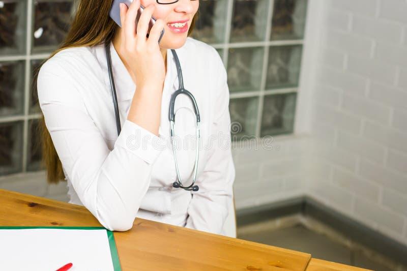 Glimlachende Vrouwelijke Arts Relaxing op haar Kantoor terwijl het Roepen aan iemand die een Mobiel Telefoonclose-up gebruiken stock foto