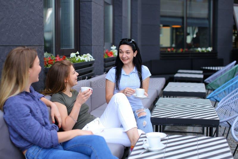 Glimlachende vrouwelijke bij koffie lachen en vrienden die, het drinken koffie roddelen royalty-vrije stock foto's